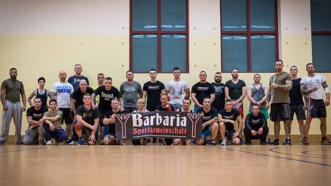 """Seminar beim Nazi-Gym """"Barbaria Schmölln"""": links unten neben dem Banner: Cheftrainer Martin Langner. Rechts mit oliv-grünem Shirt: Christoph Mohrmann, daneben in weißem Shirt: Jörn Grams"""